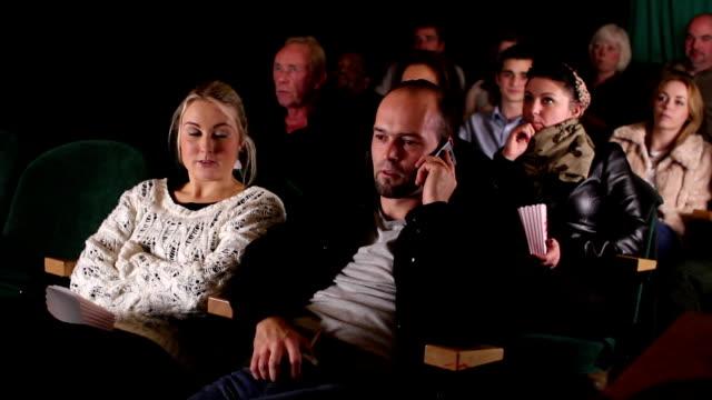 stockvideo's en b-roll-footage met man on phone incinema / movie theatre, watching film - stilte