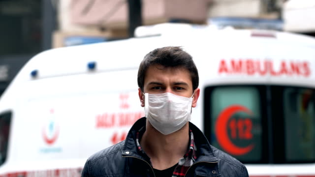 man on public area with face mask. ambulance on background. coronavirus prevention. - paramedic stock videos & royalty-free footage