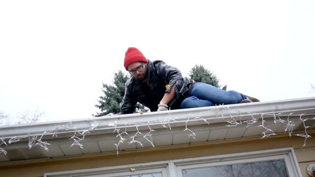 mannen på taket av ranch hus rengör sin hängrännor - version 1 - roof farm bildbanksvideor och videomaterial från bakom kulisserna
