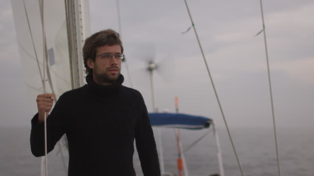 Man on sailing boat in the sea looking forward. video