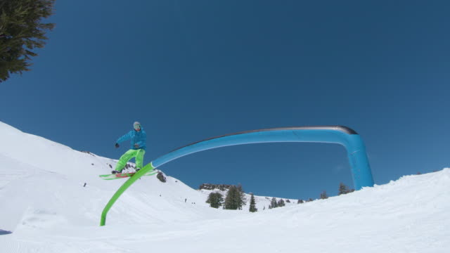 low angle: man on snowboard grinds the rail set in the middle of the ski slopes. - grindare video stock e b–roll