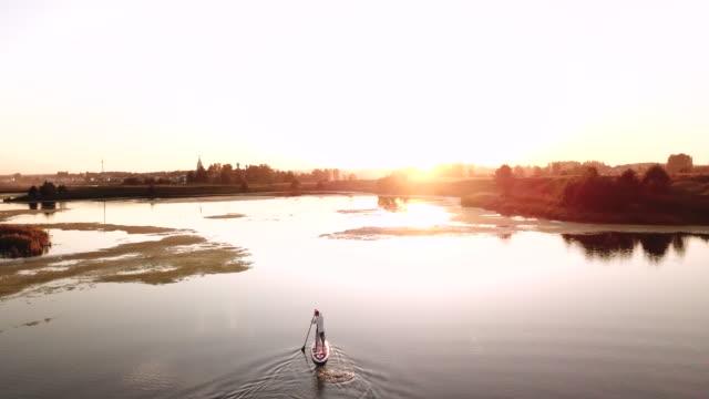 stockvideo's en b-roll-footage met man op supboard in het rustige overwoekerd meer op zonsondergang achtergrond - paddle