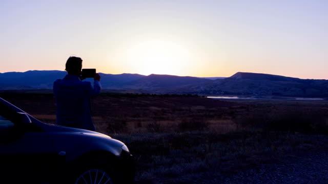 車の男は、タブレットによって山の夕日のビデオを撮影します。 ビデオ