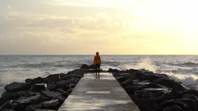Man on the jetty looking at the sea, yellow jacket in the sunset, Levanto, Italy A man on the boy on the famous Levanto pier looking at the sea with waves, opens his arms, walks, slowmotions, sunset jetty stock videos & royalty-free footage
