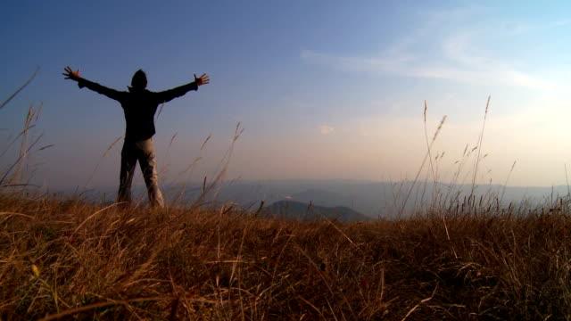 vídeos de stock, filmes e b-roll de homem no topo de uma colina - largo descrição geral