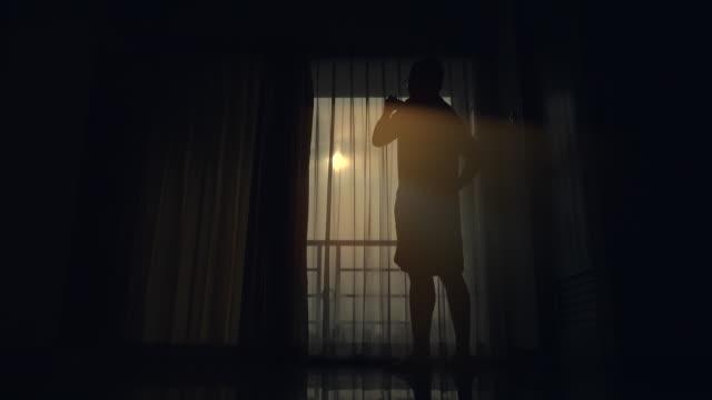 vídeos de stock e filmes b-roll de man open curtain watch sunrise - open window