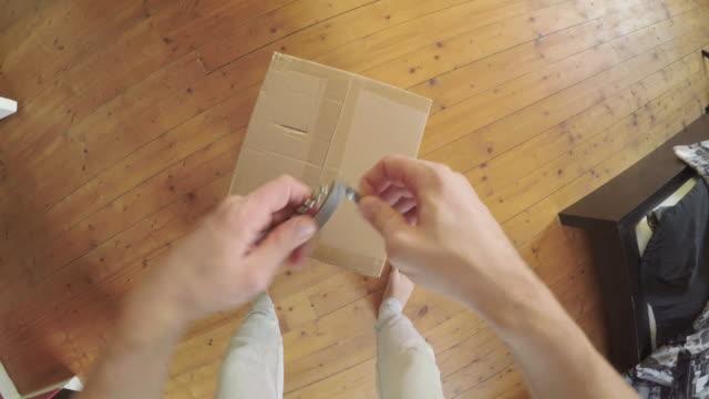 vídeos de stock e filmes b-roll de man opening a package pov - cardboard box