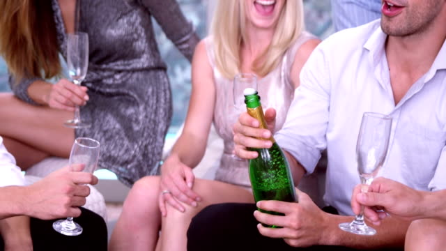 Man opening and serving friends champagne video