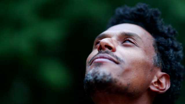 Man opening eyes looking at the sky feeling presence of divinity and God
