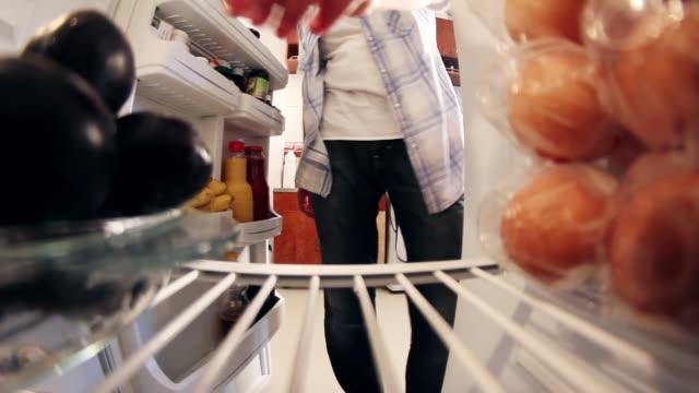 vídeos de stock e filmes b-roll de man opening fridge door to get fruits(plums) and closes door - congelador