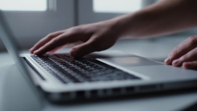 Man opening laptop and starts typing on keyboard of computer, close-up.