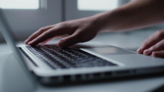 男子打開筆記本電腦,並開始在鍵盤上打字,特寫。 - 打開 個影片檔及 b 捲影像
