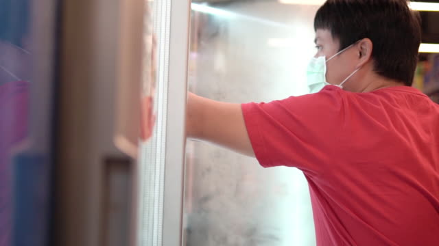 Man Opening Refrigerator in Supermarket with bare hand. Man Opening Refrigerator in Supermarket with bare hand. freezer stock videos & royalty-free footage