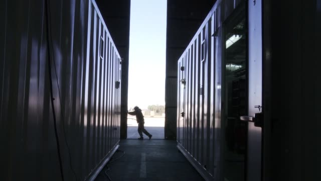 vídeos de stock e filmes b-roll de man opening the door of a container warehouse. - store