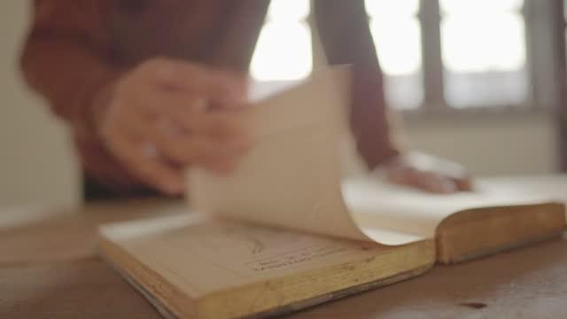 en man öppnar en bok och läser på ett träbord - lagbok bildbanksvideor och videomaterial från bakom kulisserna