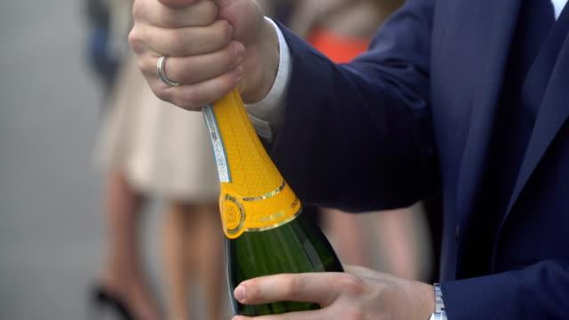 man öffnet eine flasche champagner - champagner toasts stock-videos und b-roll-filmmaterial