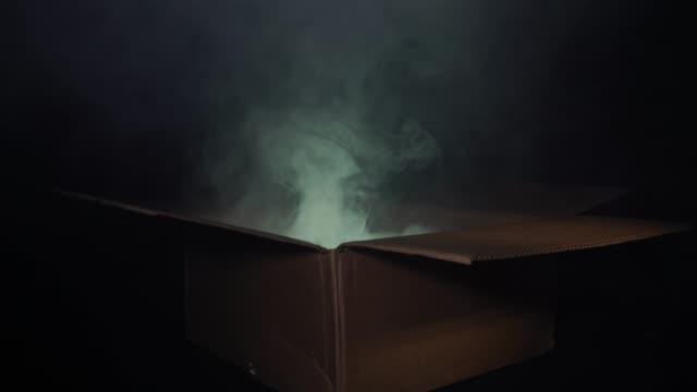 un uomo apre una scatola di cartone da cui proviene il fumo e brilla una luce multicolore. il concetto di magia e magia, sorpresa - mitologia video stock e b–roll
