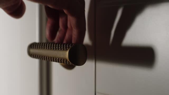 close up: man öffnet eine tür im raum mit dem türgriff im haus - mann tür heimlich stock-videos und b-roll-filmmaterial