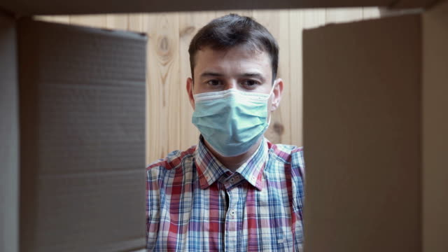 A man opens a home delivery box. Food delivery during quarantine. Self isolation, pandemic and coronavirus concept. - vídeo