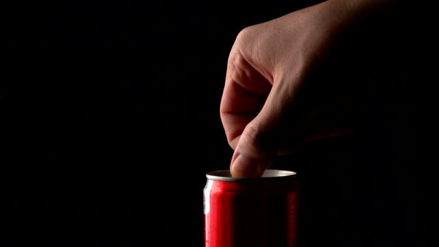 Man opens foamy cola can. Slow motion shot against black background video