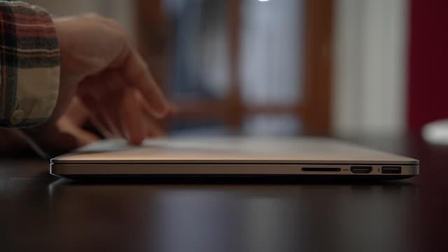 vídeos de stock, filmes e b-roll de homem abre laptop no escritório - abrindo