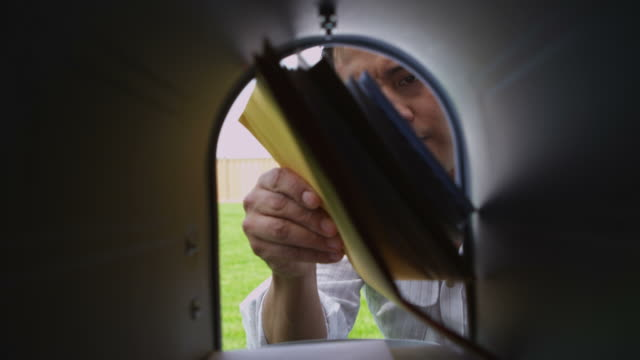 Man opens mailbox and gets letters