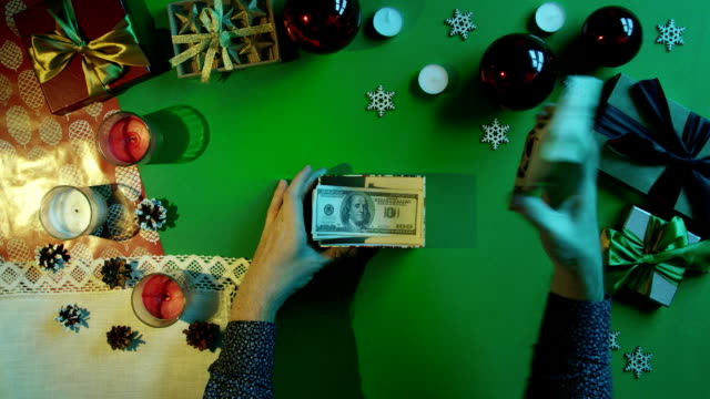 男はクロマキー、トップ ショット ダウンと内部テーブルの上のドルを新年のギフト ボックスを開きます ビデオ
