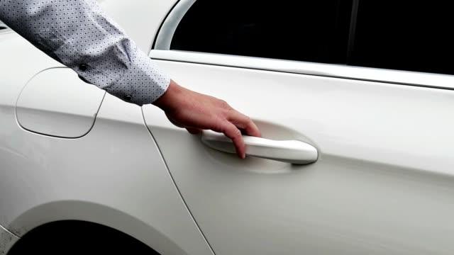 a man opens the door of a white car. - sportello d'auto video stock e b–roll