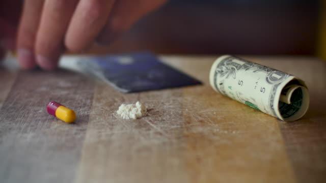 man öppnar upp en kapsel med droger i dem och gör linjer med det vita pulvret - amfetamin pills bildbanksvideor och videomaterial från bakom kulisserna
