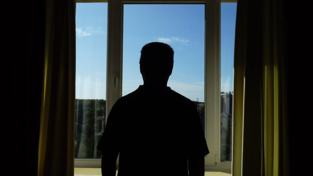 A man opens window curtains in the morning and makes physical jerks. The rays of the sun shine into the room. video