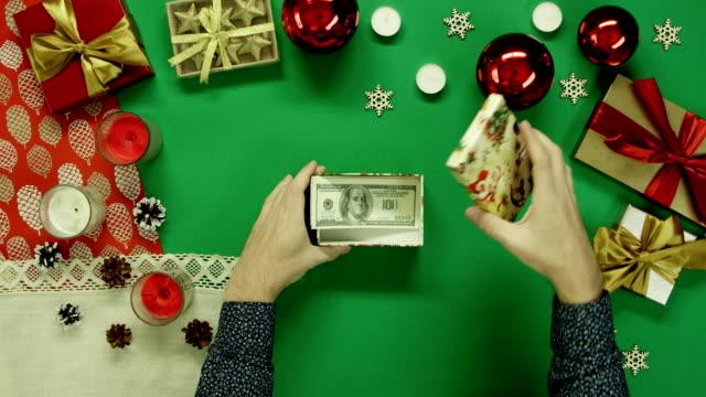 男は、クロマキー、トップ ショット ダウンと内部テーブルの上のドルをクリスマス ギフト ボックスを開きます ビデオ