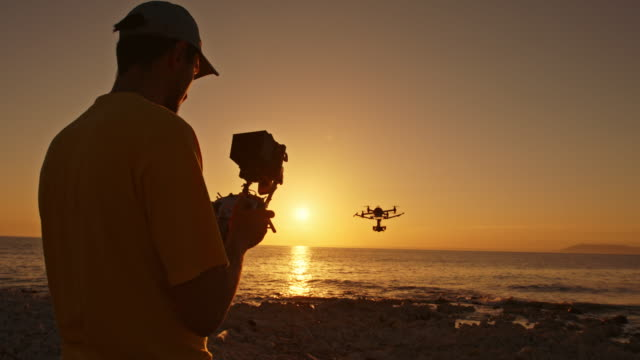 Man operating a drone from the beach at sunset video