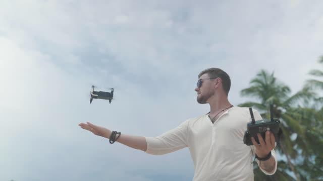 man operating a drone with remote control - telecomando background video stock e b–roll