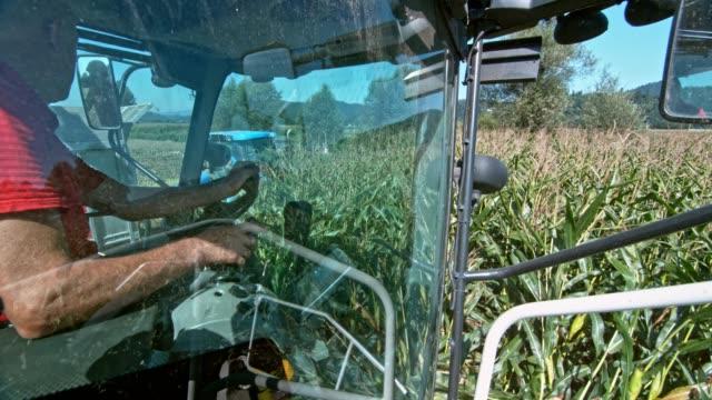 SLO MO Man operating corn harvester in field
