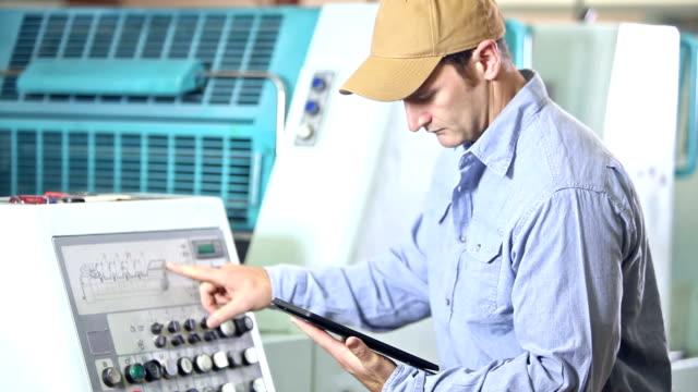 Man operating printing press, setting controls video