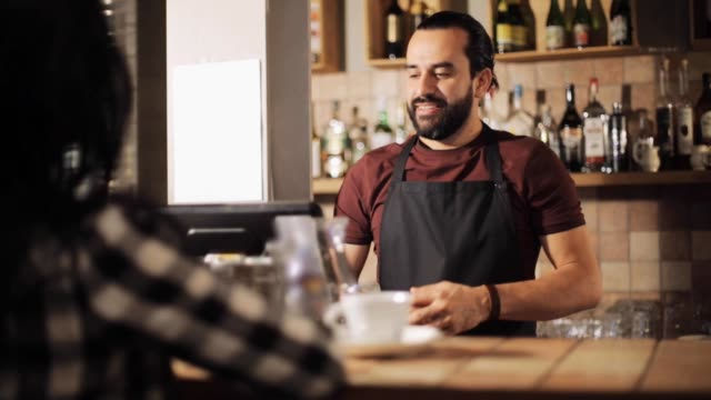 man or waiter serving customer in coffee shop video