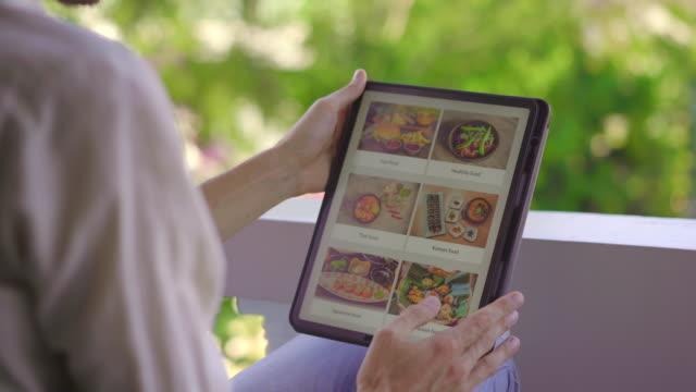 bir adam tablet kullanarak öğle yemeği için online yemek sipariş. online shoping kavramı - sipariş vermek stok videoları ve detay görüntü çekimi