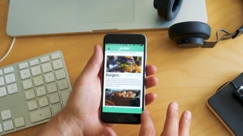 vídeos de stock e filmes b-roll de man orders food with app on smartphone - food