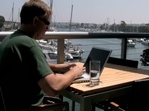 man outside working on laptop, waves to passing boat - one mature man only stock videos & royalty-free footage