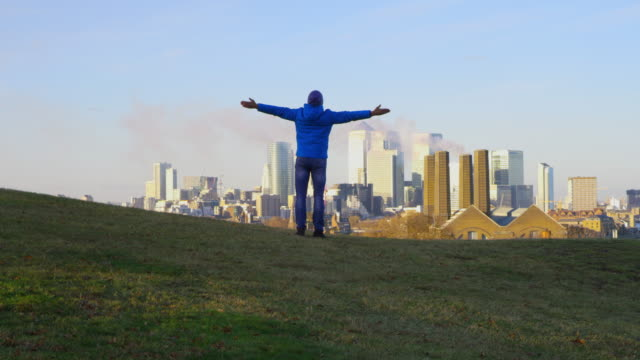 WS Man outstretching his arms above the city video