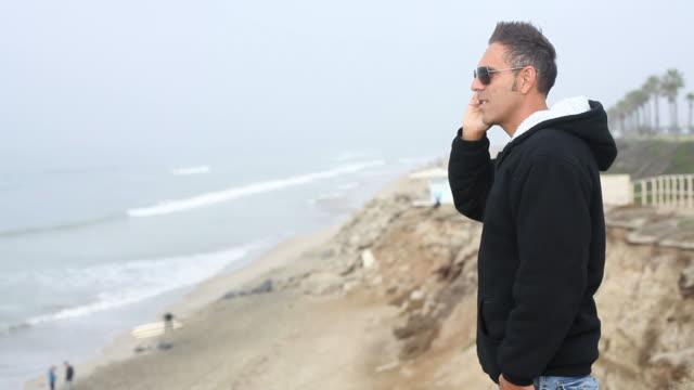 man overlooking ocean talking on cell phone - bir orta yetişkin erkek sadece stok videoları ve detay görüntü çekimi