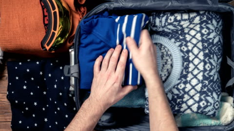Man packing a luggage for winter holidays for his girlfriend. Timelapse Man packing a luggage for winter holidays for his girlfriend. Timelapse continuity stock videos & royalty-free footage