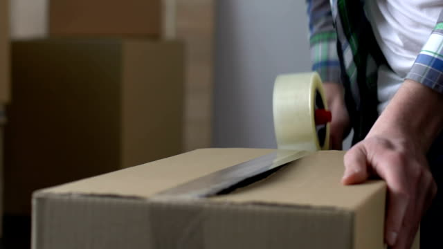 Man packing cardboard box with adhesive tape, moving out, migration, life change