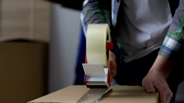 Man packing carton, relocation, moving service worker helping on background video