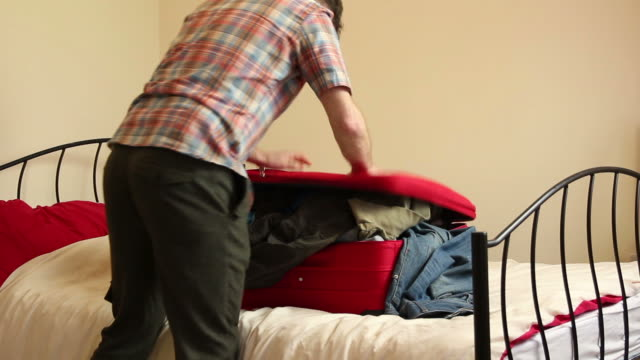 Man packing his suitcase - Hard to close! video