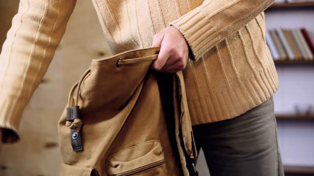 vídeos de stock e filmes b-roll de man packing his touristic backpack with favorite clothes, preparing for journey - mochila saco