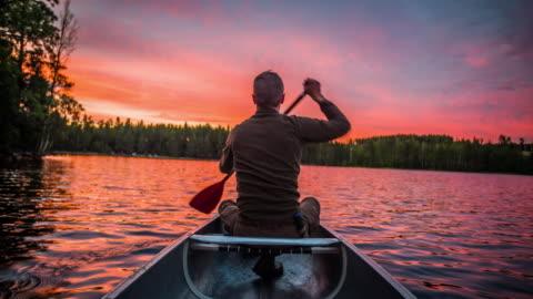 vídeos y material grabado en eventos de stock de hombre remando una canoa al atardecer - pov - viajes