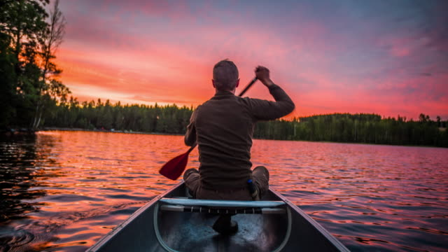 Man paddling a canoe at sunset - POV video