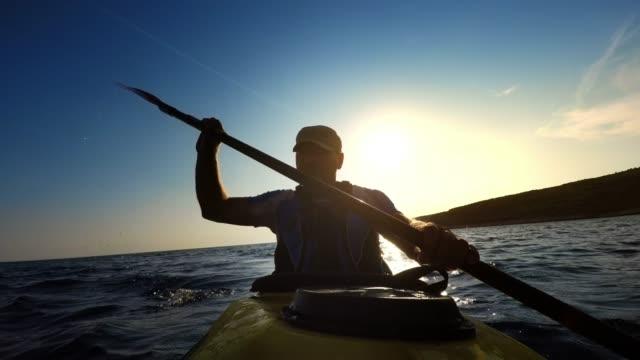 LD Man paddling a sea kayak along the coastline