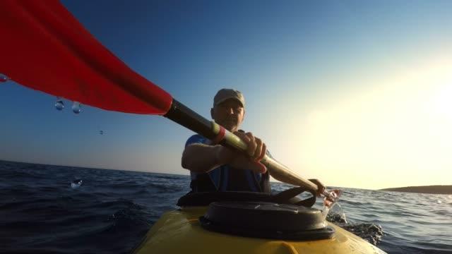 LD Man paddling a sea kayak at sea in late afternoon sun